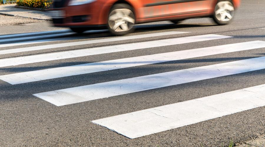 Pedestrian crossing with orange car speeding past