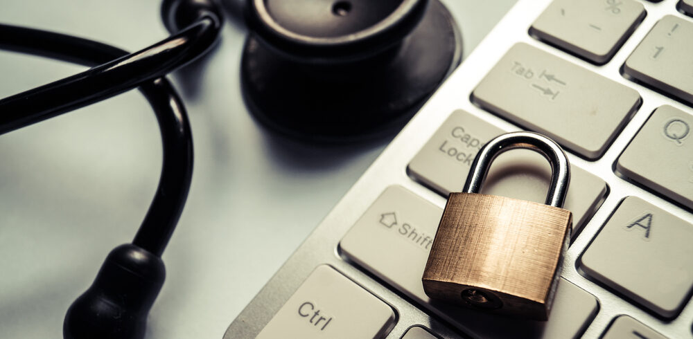 A padlock on a laptop resting next to a stethoscope to signify a data breach of medical information
