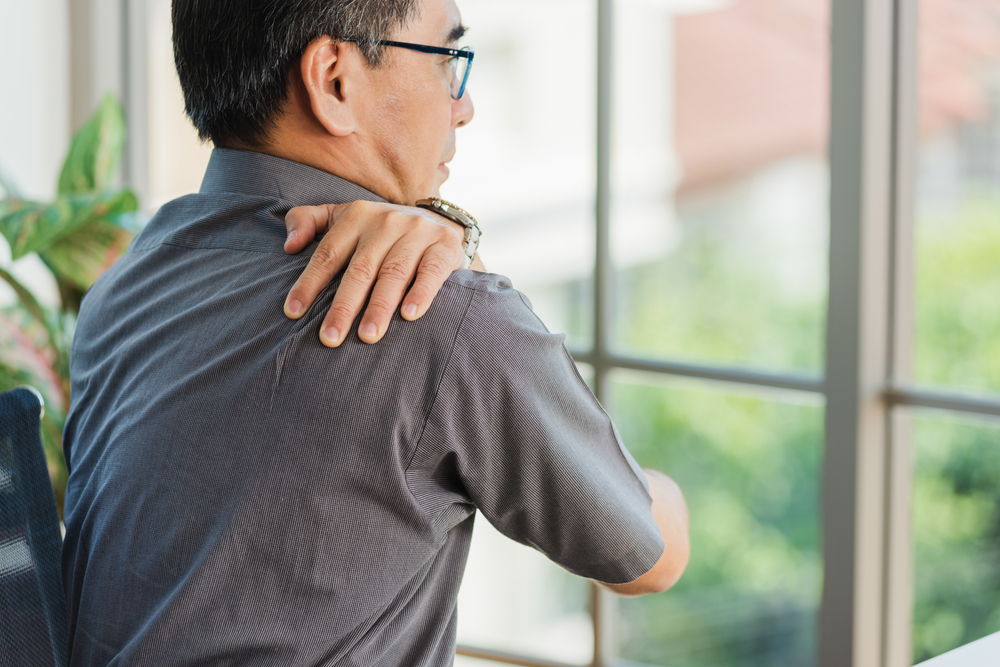 Photograph of man in a grey shirt holding his injured shoulder and looking out of the window