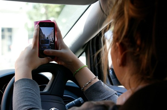 Young woman using her phone to take a picture whilst driving