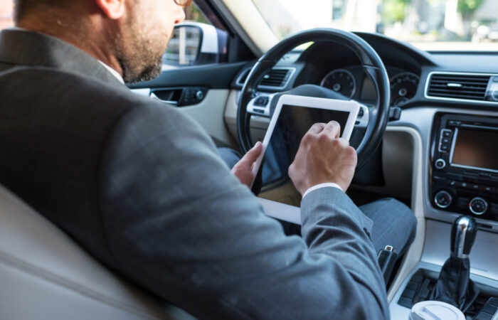 Photograph of man in suit video calling on his tablet whilst driving