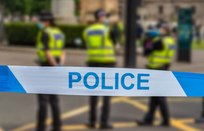 Colour image of 3 police officers standing on the street on a scene behind police tape