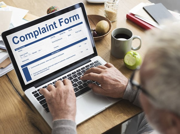 Man using a silver laptop on ICO website complaint form