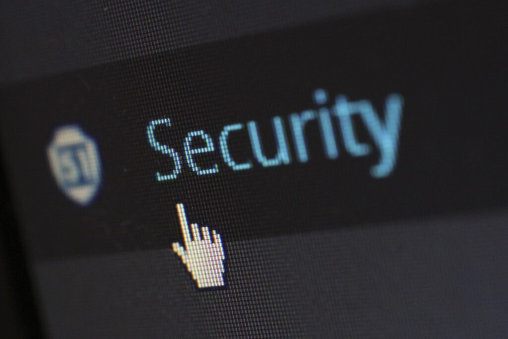 Zoomed in image of computer screen with the cursor on the word Security written in blue against a black background