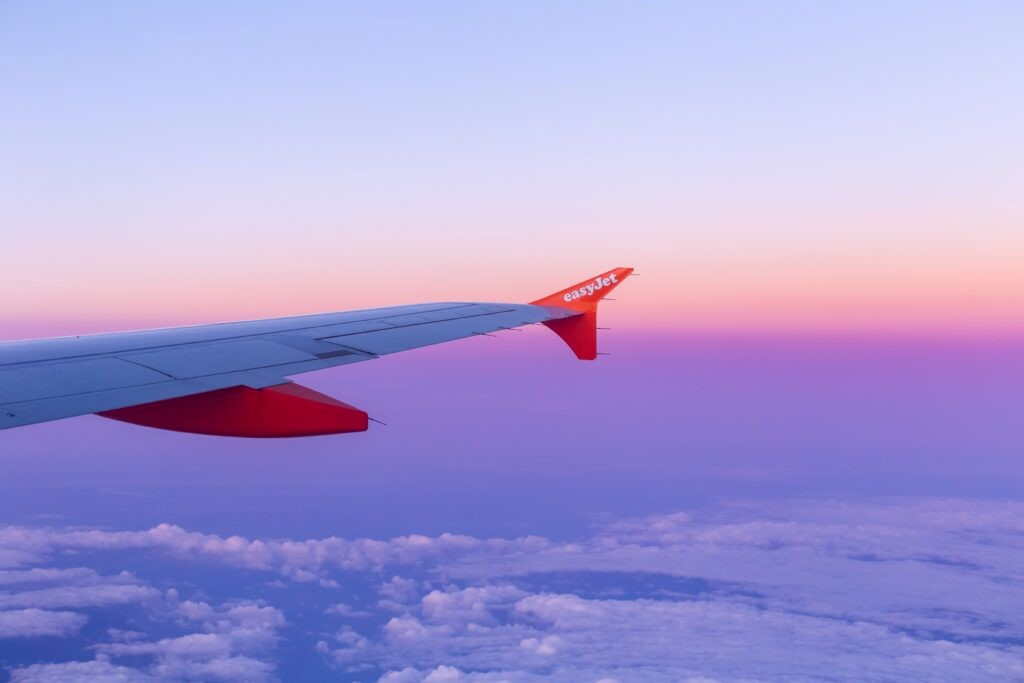 An Easy Jet plane flying over a sunrise